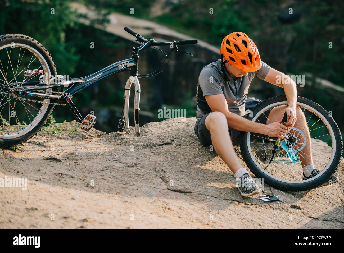 young trial biker fixing bicycle wheel outdoors while sitting on stone - Stock Image