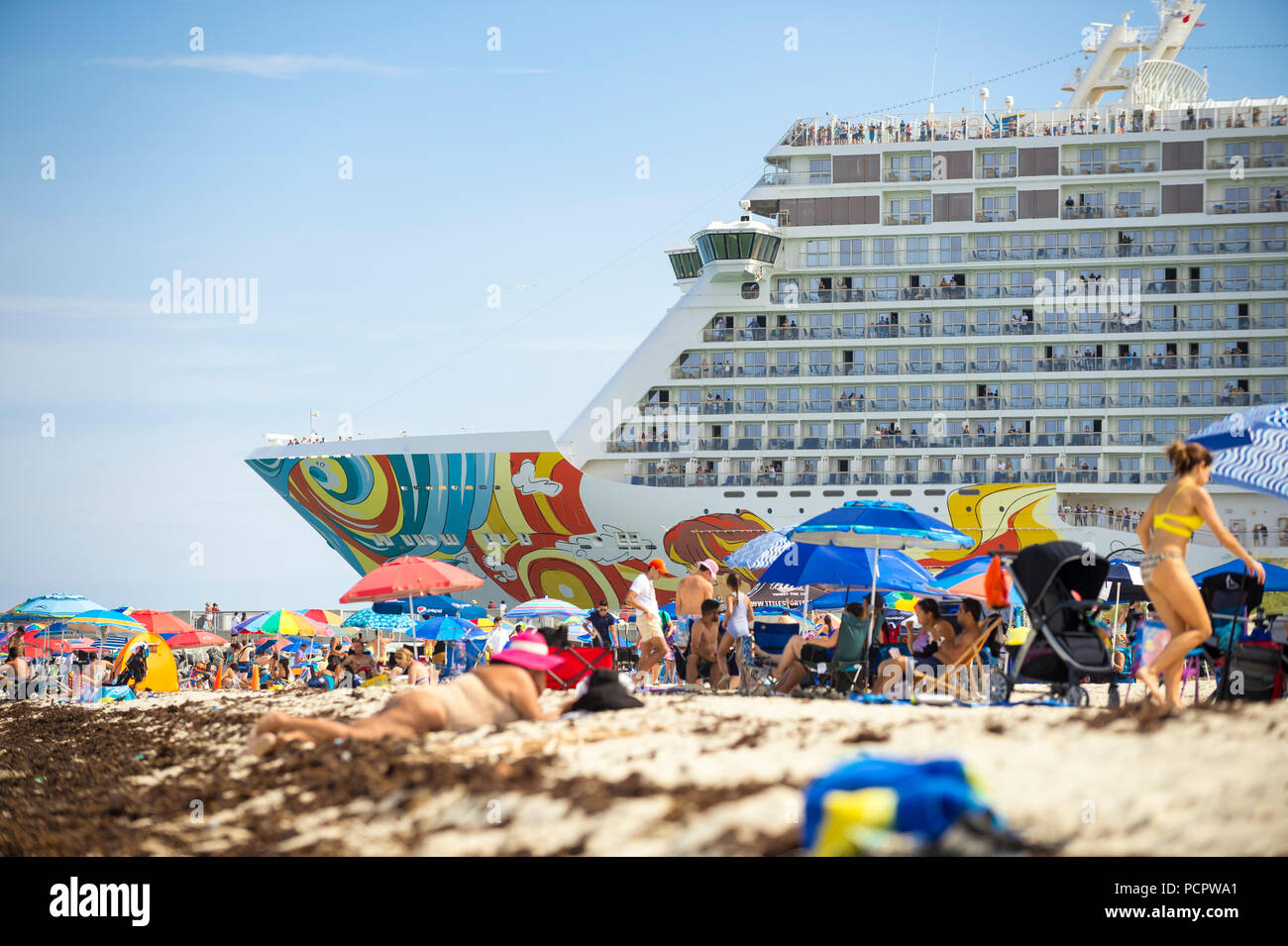 MIAMI - CIRCA JUNE, 2018: Norwegian Getaway cruise ship leaves port and passes South Beach busy with sunbathers. - Stock Image