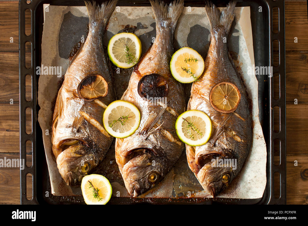 Fish dorada on a frying pan. Eating a healthy diet. Top view. - Stock Image