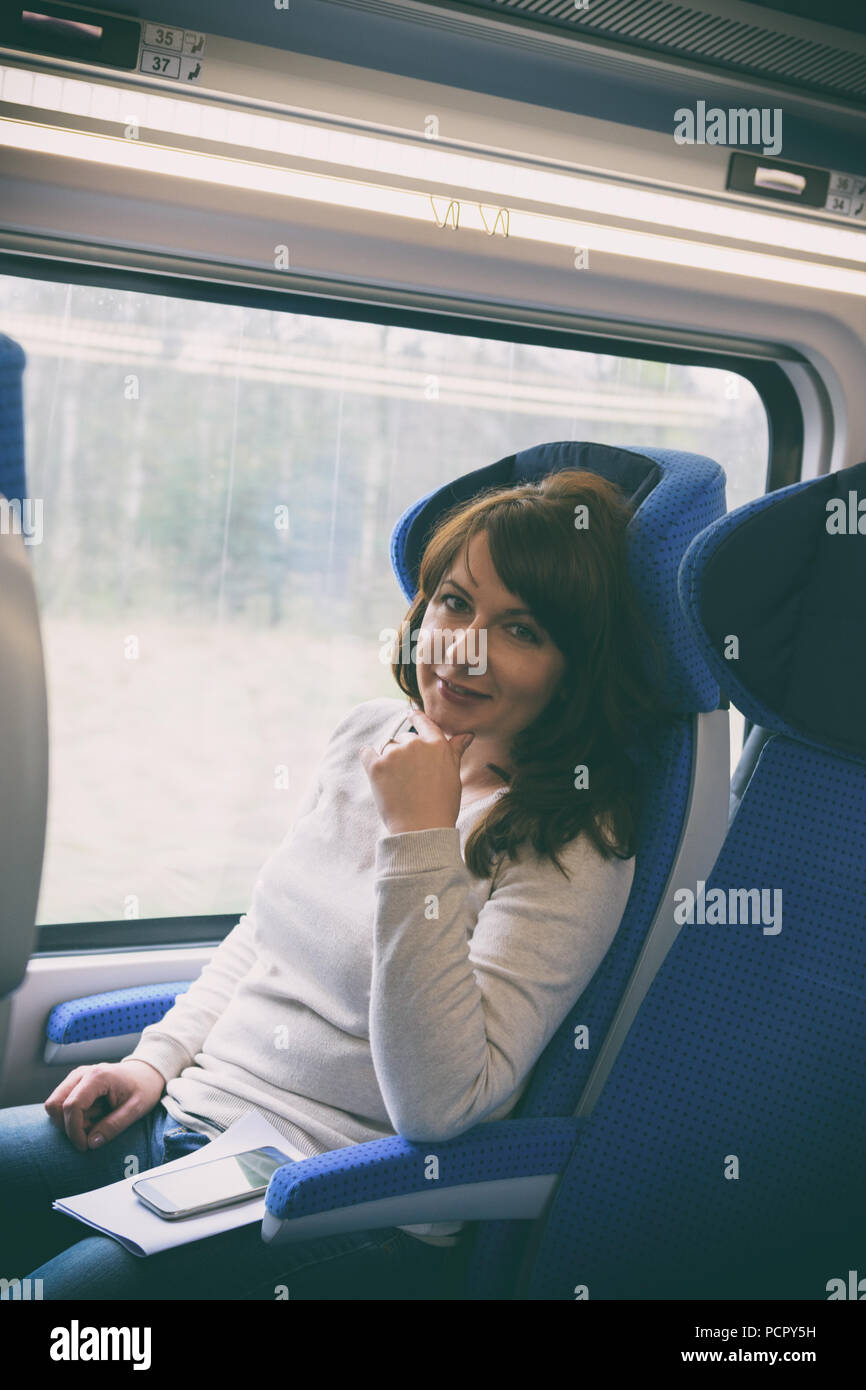 Caucasian woman traveling by train on window seat, with smartphone and papers on her leg - Stock Image
