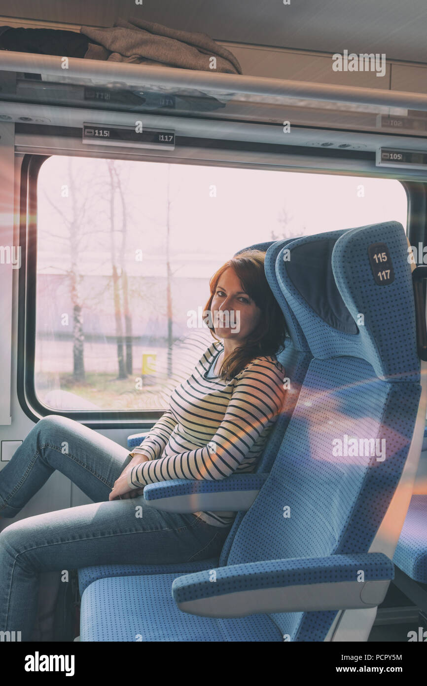 Caucasian woman traveling by train on window seat - Stock Image