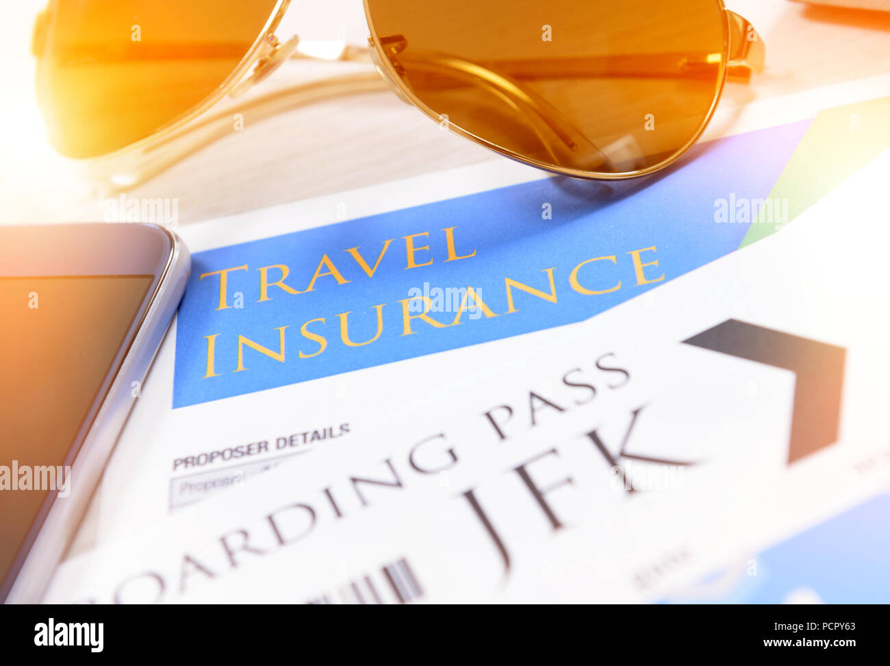 Airline boarding pass tickets with travel insurance,  sunglasses, mobile phone - Stock Image
