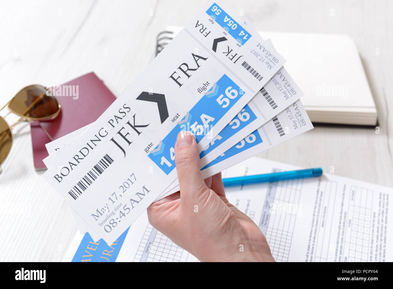 Airline boarding pass tickets in haand with travel insurance, passports, sunglasses, pen and notebook as a concept of traveling - Stock Image