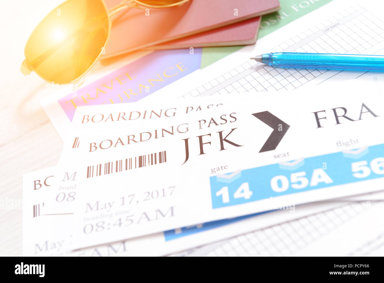 Airline boarding pass tickets with travel insurance, passports, sunglasses, pen as a concept of traveling - Stock Image