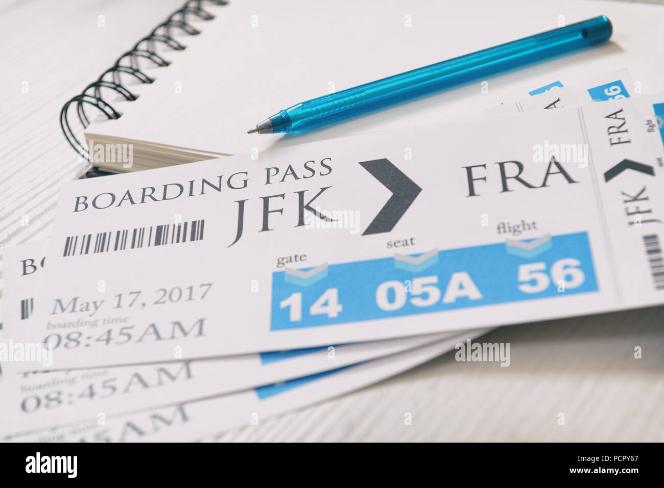Airline boarding pass tickets with notebook and pen - Stock Image
