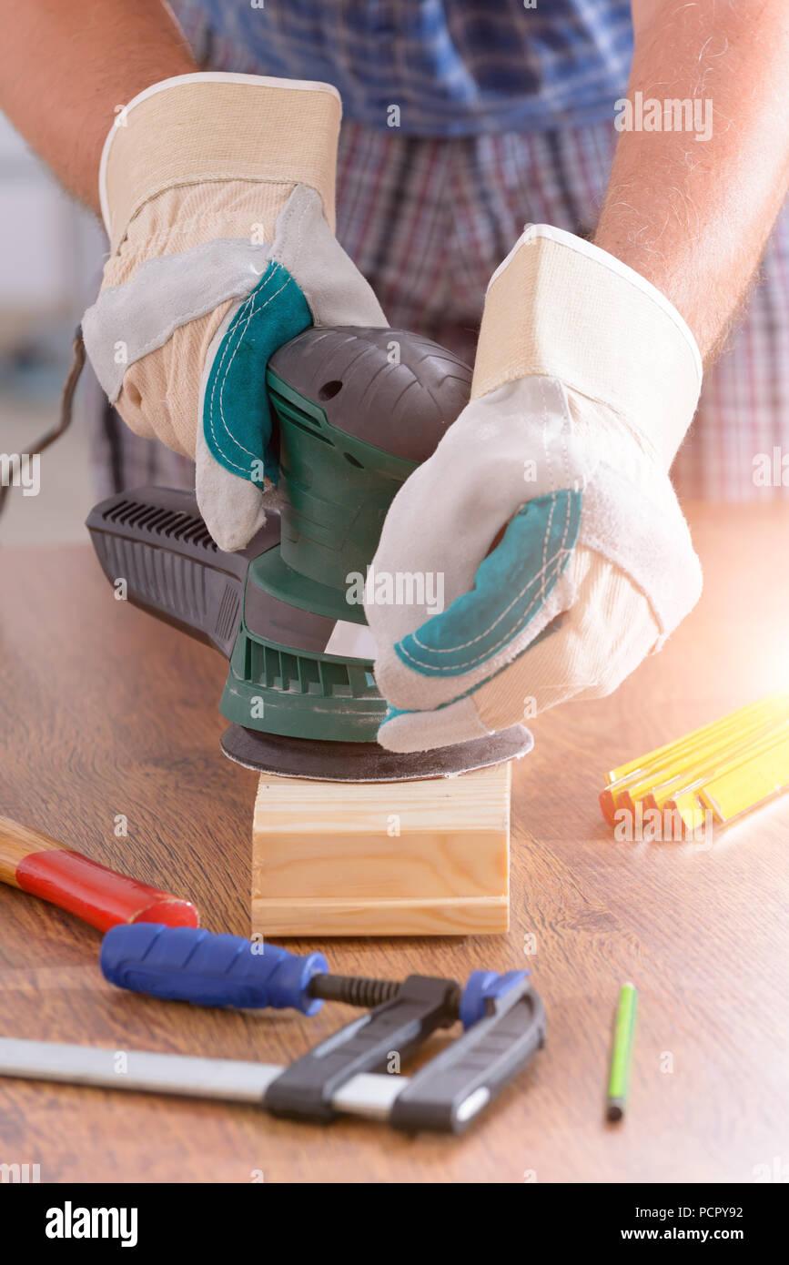 Man sanding a wood with orbital sander in a workshop - Stock Image