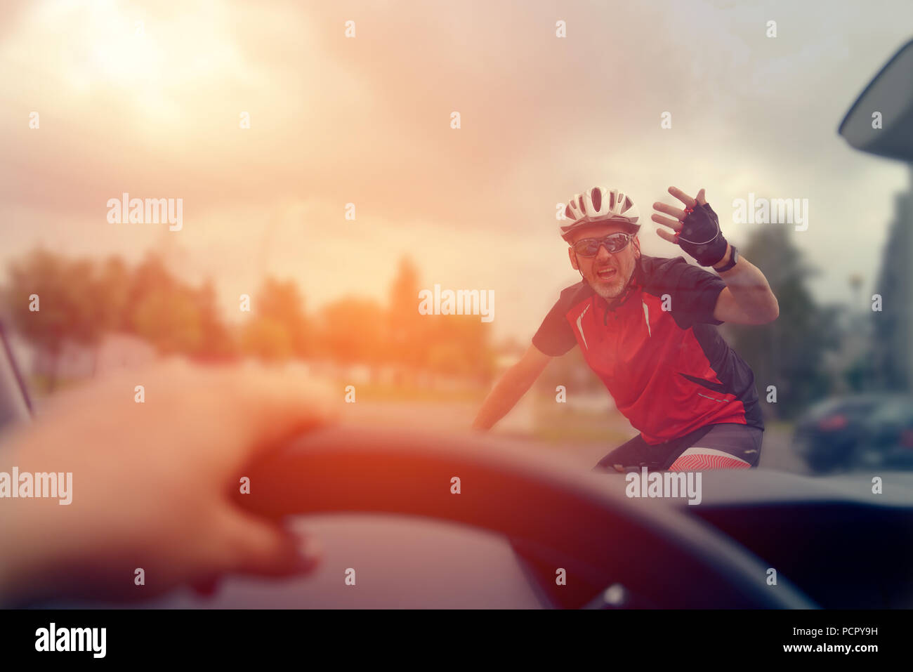 Forcing the right of way on the road for the driver of a car with the participation of a cyclist - Stock Image