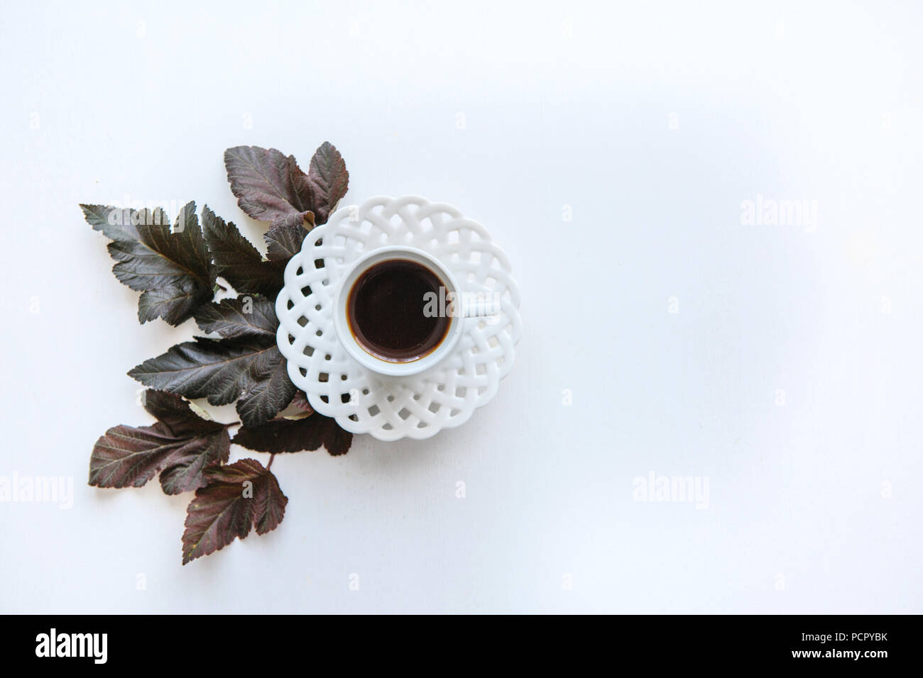 A cup of aromatic espresso or black tea. Nearby lie autumn leaves. Simple minimalistic autumn design. - Stock Image