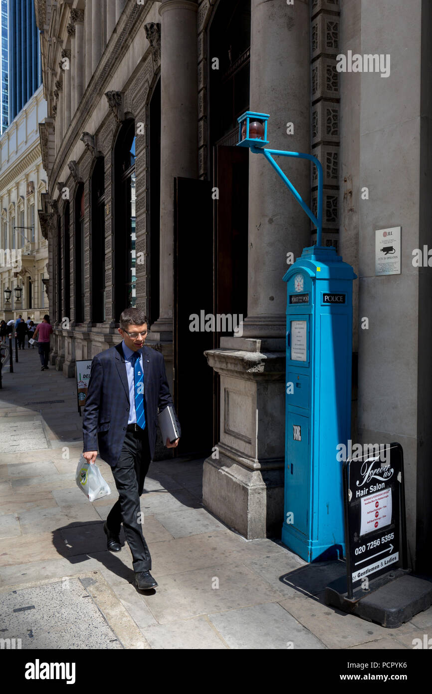 A businessman walks past one of the few remaining police signal boxes on Threadneedle Street  in the City of London, the capital's historic financial district, on 2nd August 2018, in London, England. The Police box is a public telephone kiosk or callbox for the use of members of the police, or for members of the public to contact the police. It was introduced in the United States in 1877 and was used in the United Kingdom throughout the 20th century from the early 1920s. - Stock Image