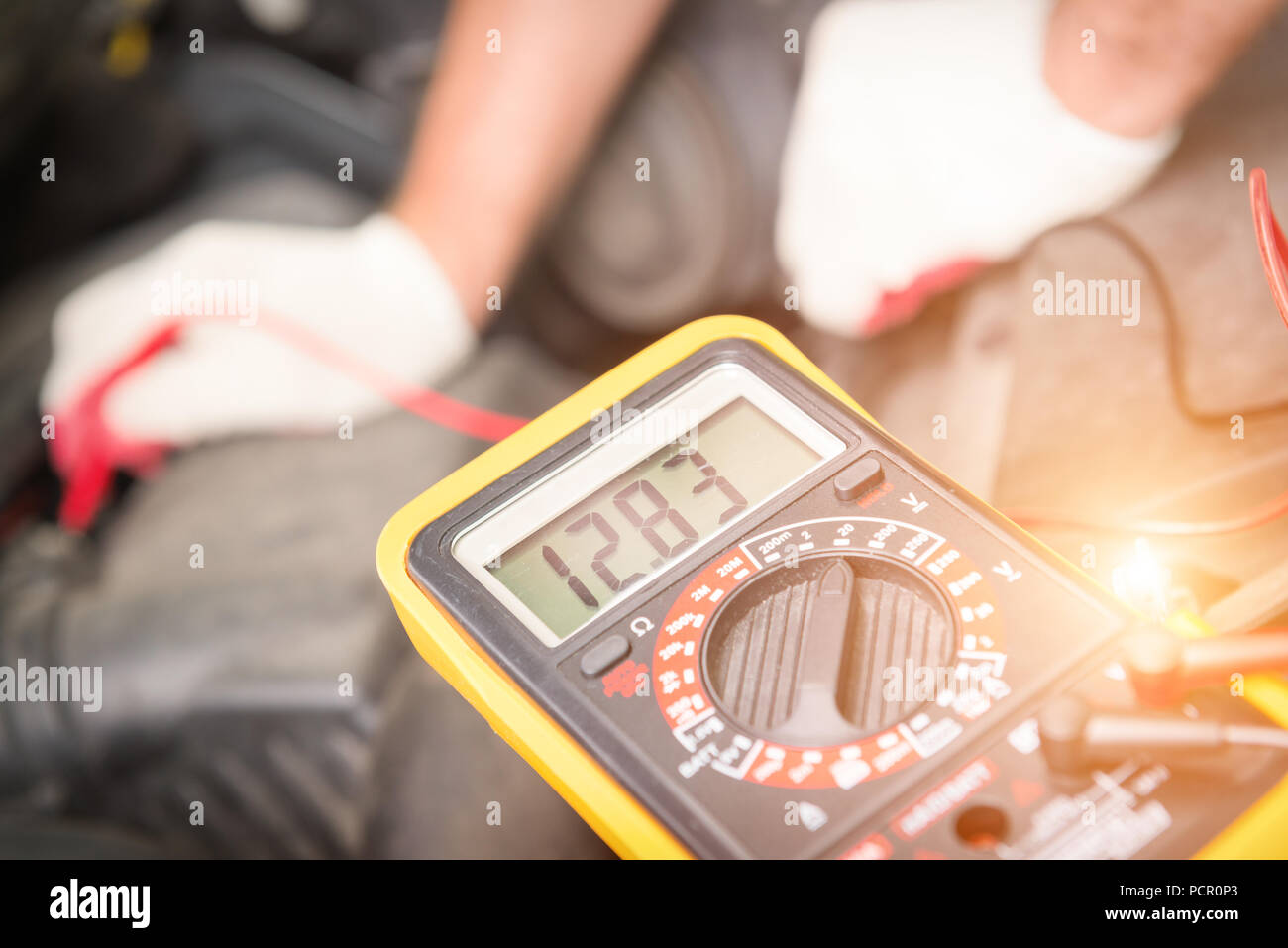 Car mechanic uses a multimeter to check car battery voltage - Stock Image