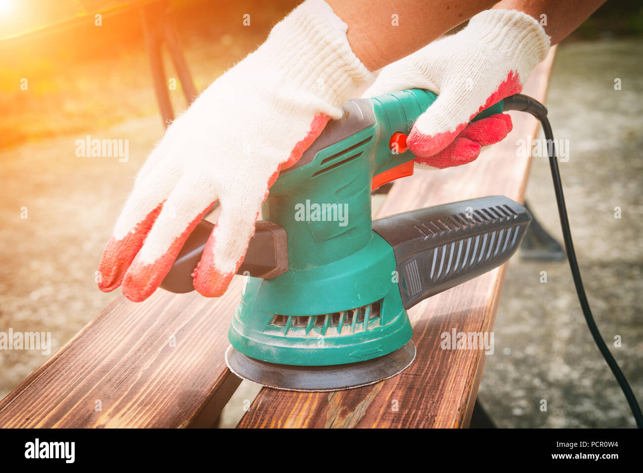 Sanding a wood with orbital sander outdoor Stock Photo
