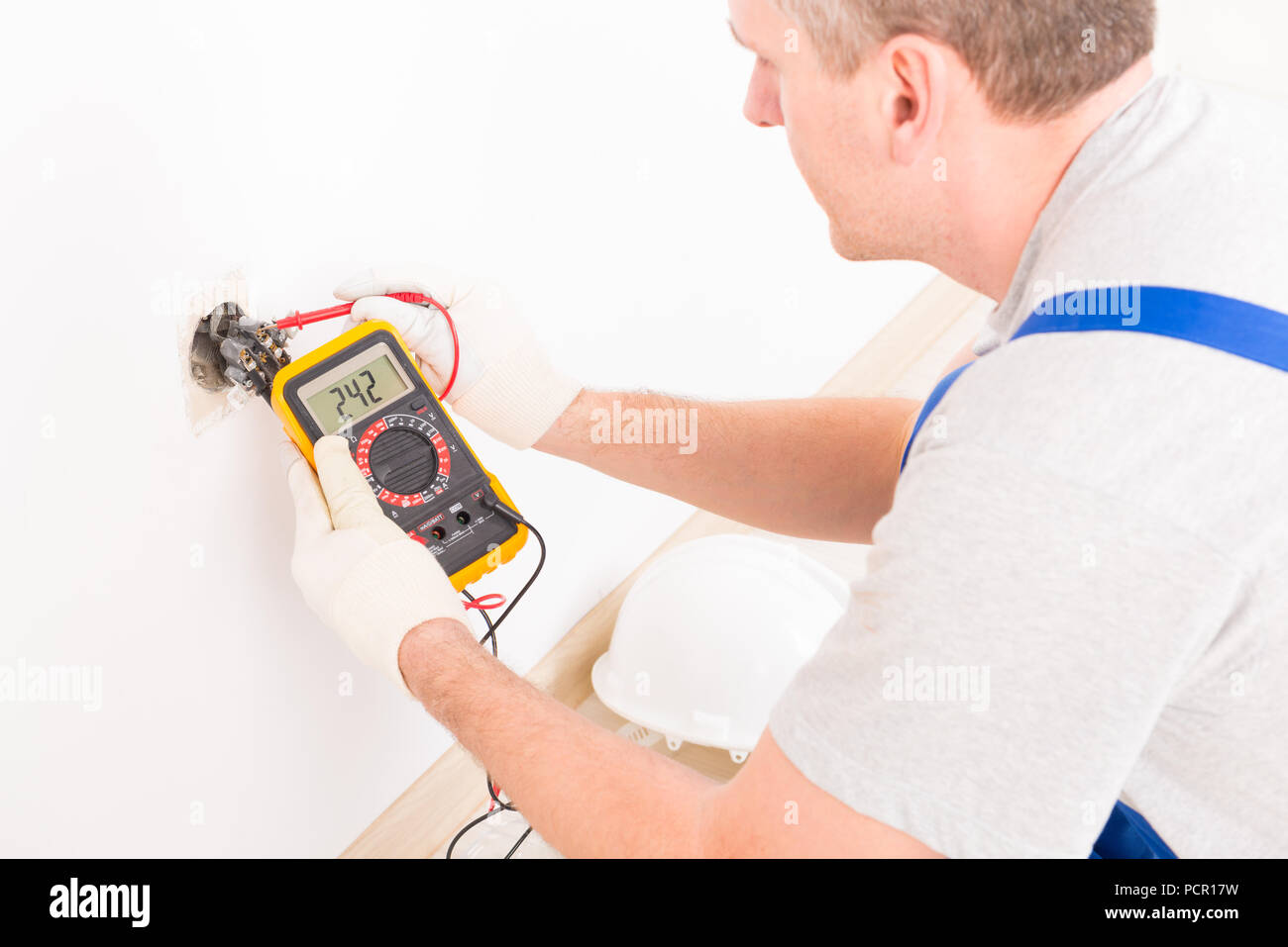 Electrician checking socket voltage with digital multimeter - Stock Image