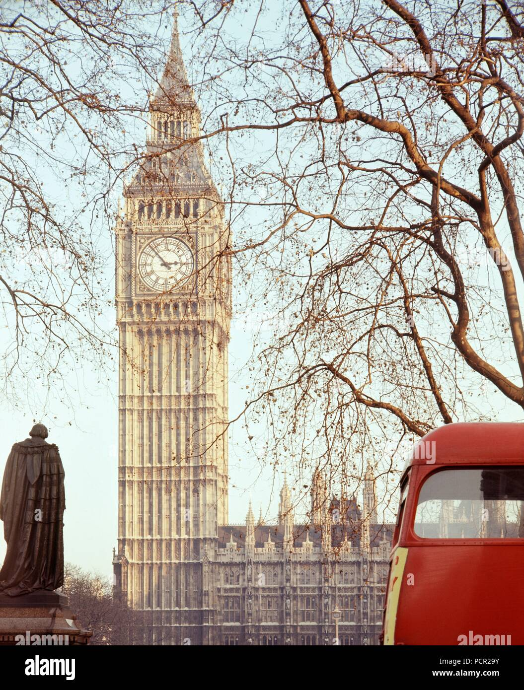 Palace of Westminster, London, c1945-c1980. The clock tower of the Houses of Parliament viewed from Parliament Square. The huge bell housed in the clock tower and known as Big Ben came into operation in 1859. A red London bus is passing. Stock Photo