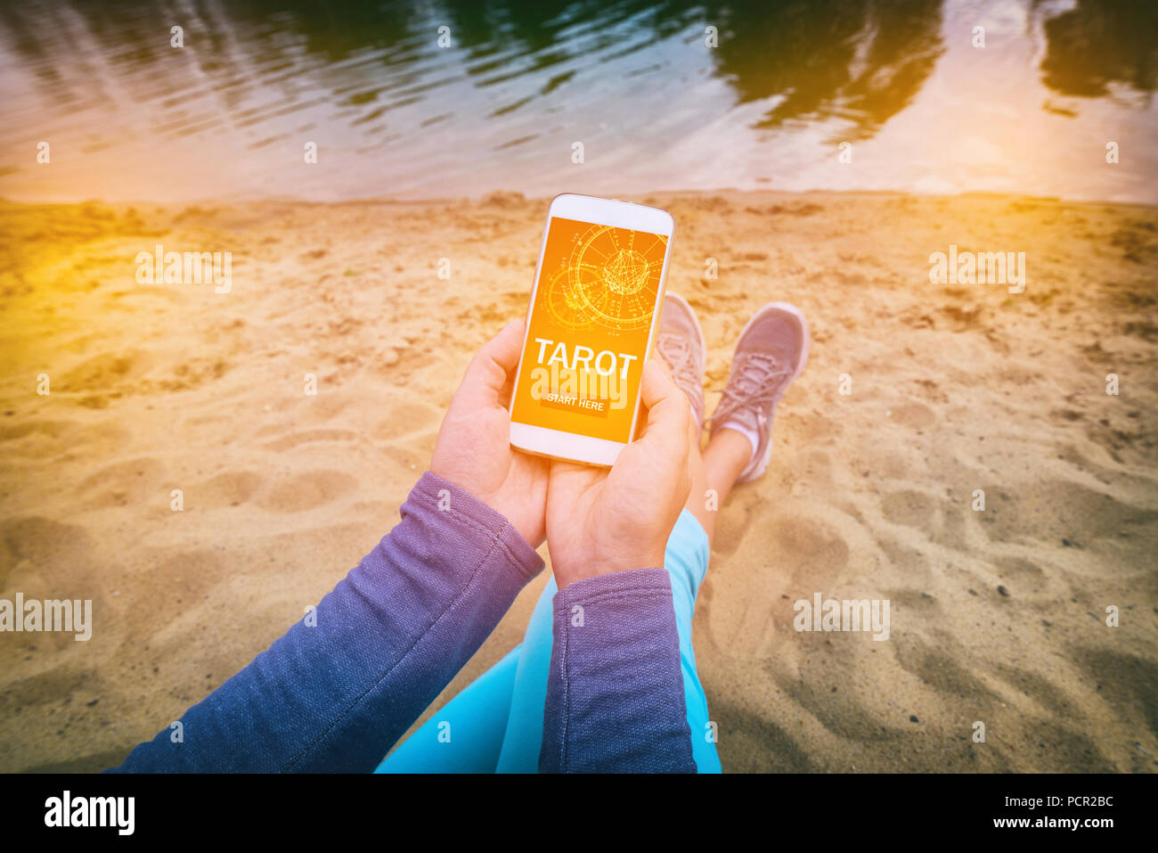 Woman holding smartphone with modern fortunetelling application on screen. Divination addiction concept - Stock Image