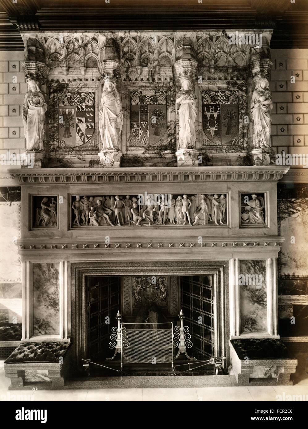 Fireplace and ornate mantlepiece in the saloon at Eaton Hall, Eccleston, Cheshire, 1887. Eaton Hall was remodelled in the Gothic style in 1870-1882 by Alfred Waterhouse for the Duke of Westminster. In 1963 the main part of the hall was demolished, and a new hall constructed. The chapel, clock tower and stables were retained. - Stock Image