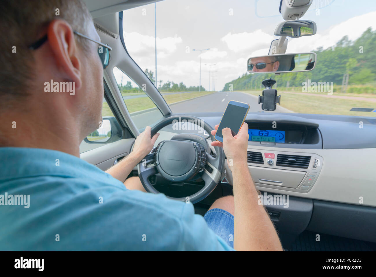 Man using phone while driving the car. Risky driving behaviors concept - Stock Image
