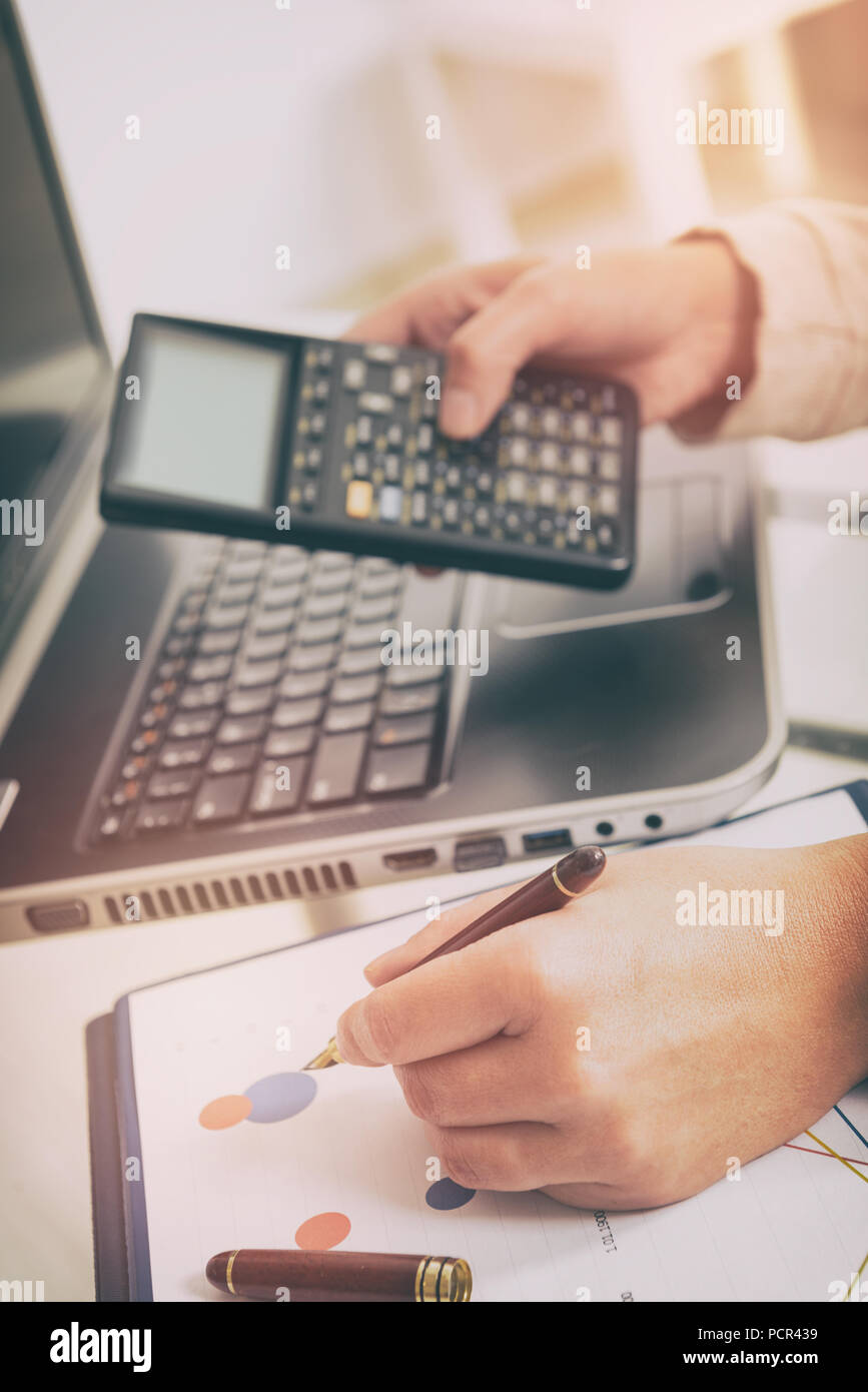 Womans hand holding calculator and writing with pen, financial chart report and notebook on desk at office. Stock Photo