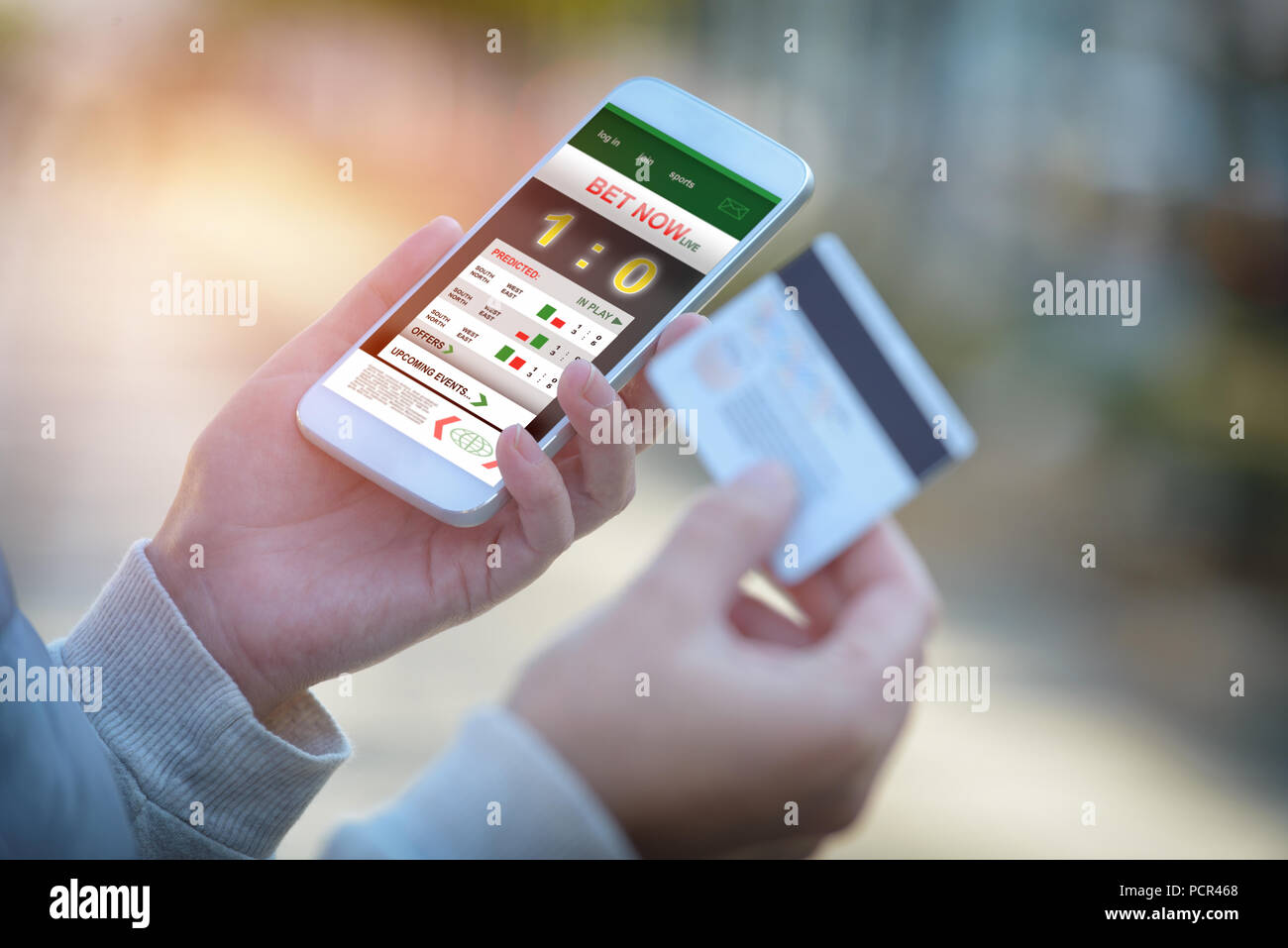 Betting on sports, holding smart phone with working online betting mobile application - Stock Image