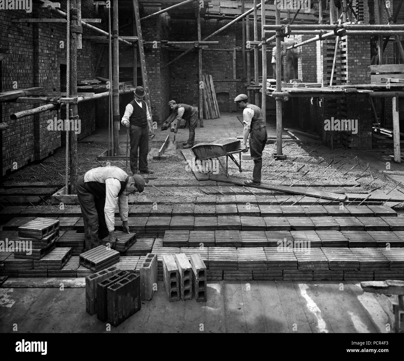 Construction workers laying a hollow pot floor, 8 Lloyds Avenue, City of London, 1907. The 'hollow pot' system, known as the Kahn system, was invented by Julius Kahn in 1903 and was much used for flooring. This building was designed by Richard Norman Shaw for Associated Portland Cement Manufacturers. - Stock Image