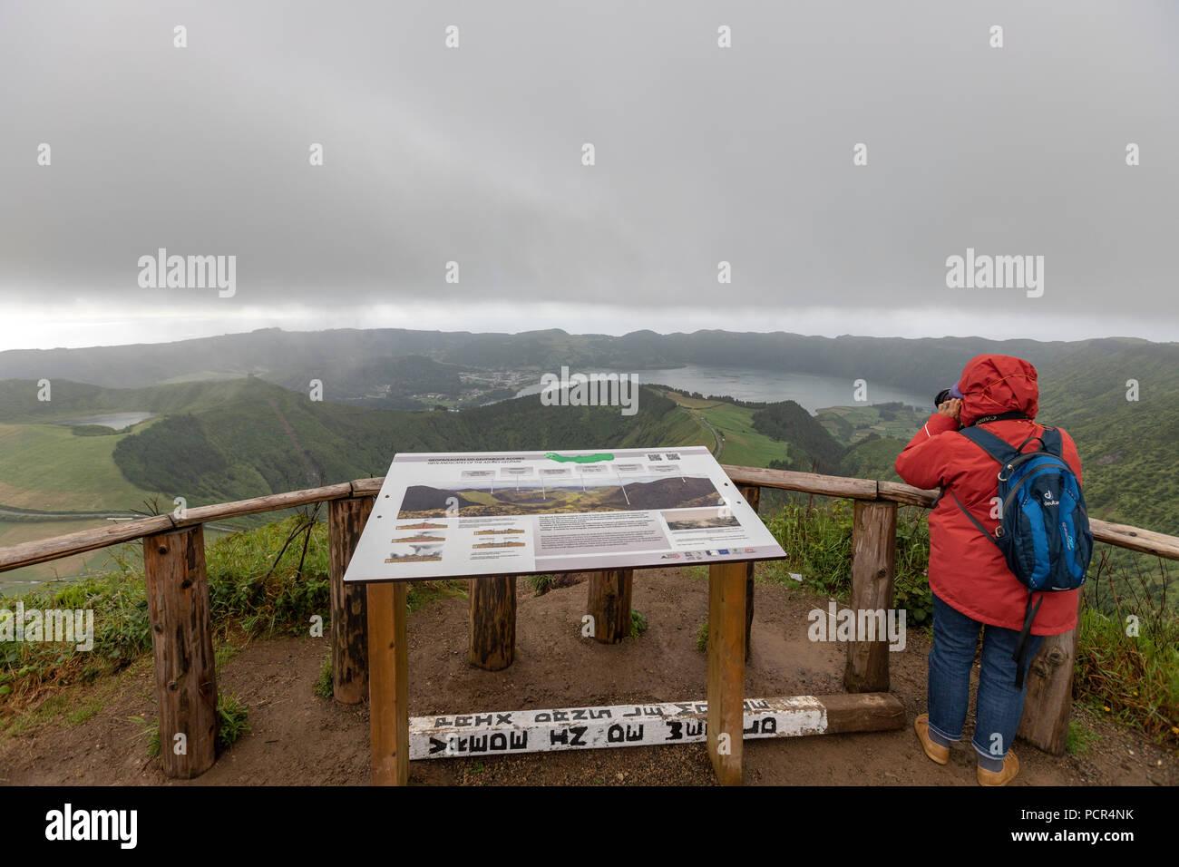 Tourist on Lagoa do Canario Miradouro, viewpoint, in a foggy and rainy day and Santiago Lake and part of Sete Cidades Lake. Sao Miguel island, Azores Stock Photo