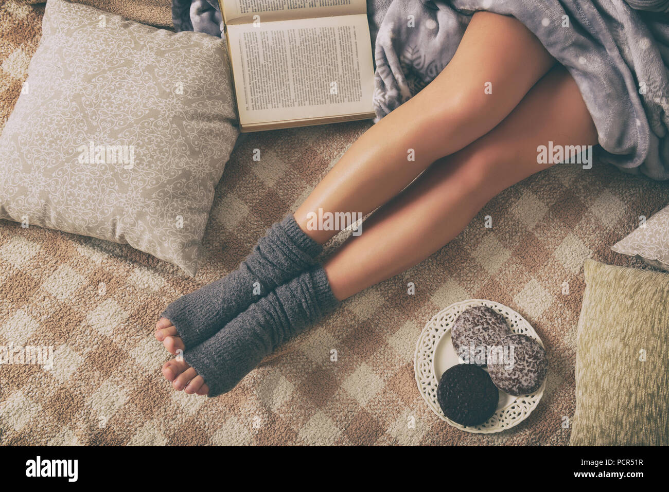 Woman with sweet gingerbread cookies, book lying on bed in the cozy room - Stock Image