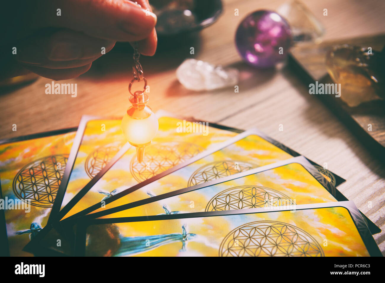 Tarot cards dowsing tool in hand and crystals as a concept of psychic advisor or ways of divination - Stock Image