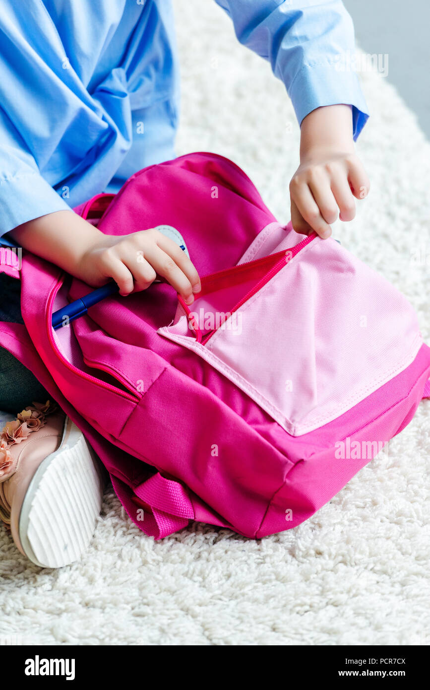 cropped shot of child packing pink school bag at home Stock Photo