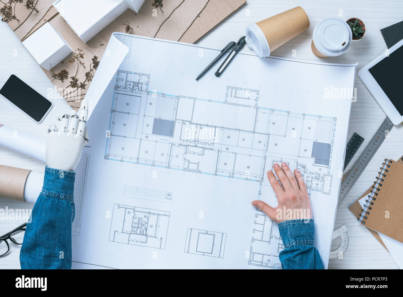 partial view of male architect with prosthetic arm working with blueprint at table with rulers, smartphone and digital tablet - Stock Image