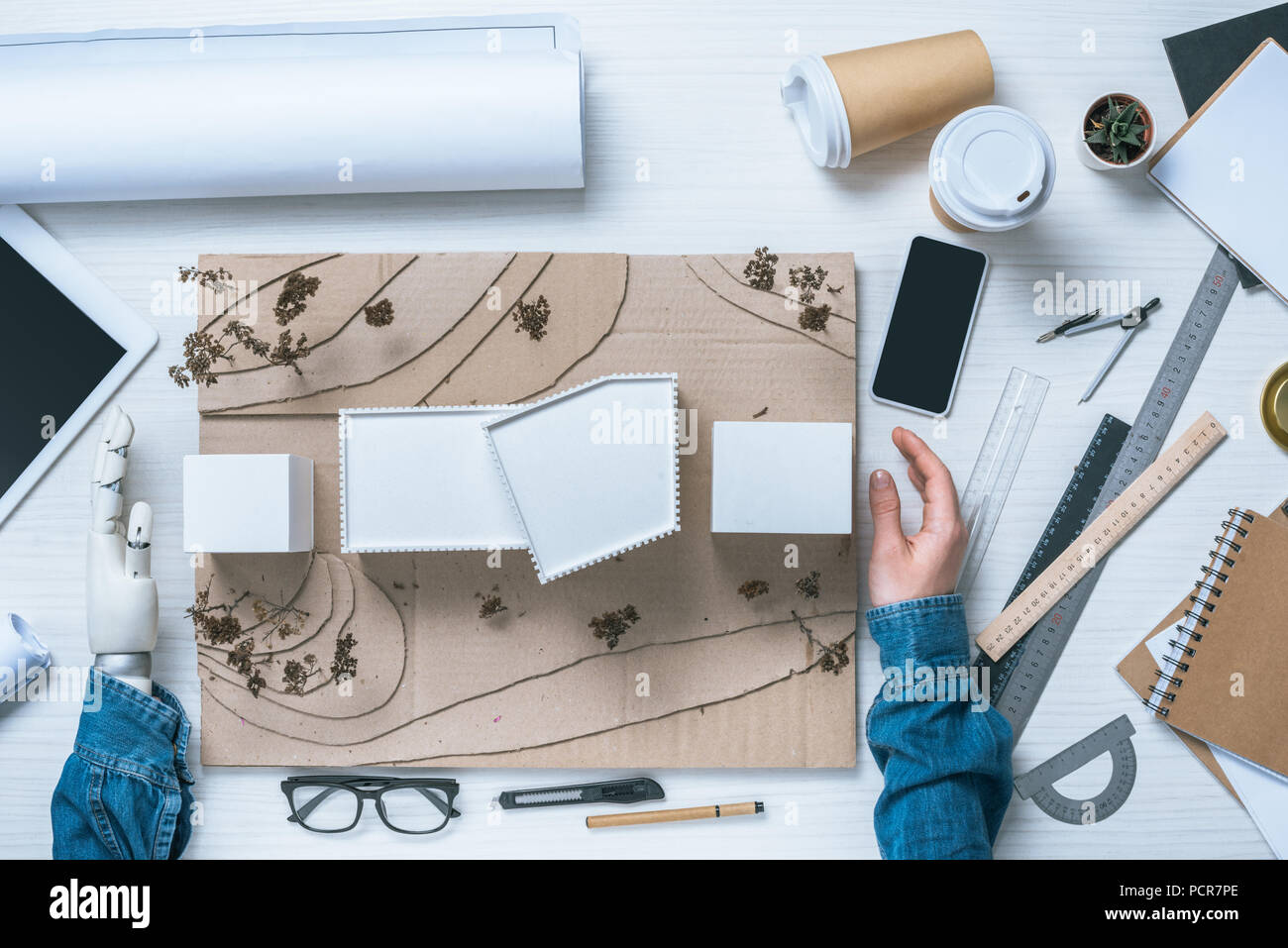 cropped image of male architect with prosthetic arm making model of house at table with coffee cups, rulers and blueprint - Stock Image