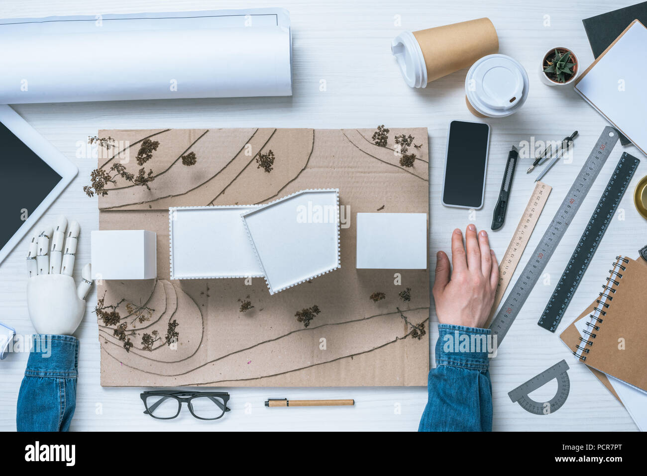 cropped image of male architect with prosthetic arm sitting at table with model of house, rulers, blueprint and gadgets - Stock Image