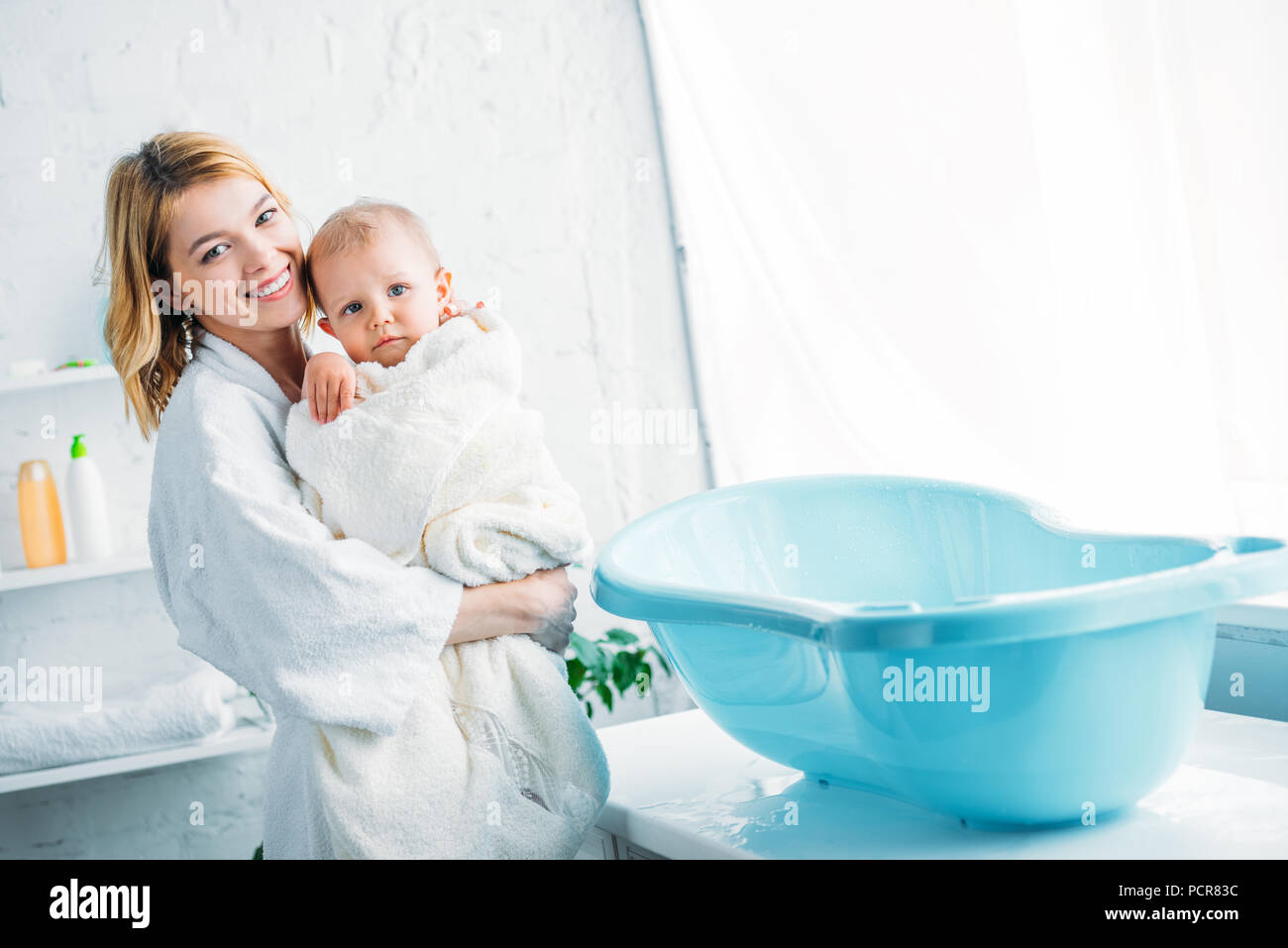 smiling mother in bathrobe carrying adorable child covered in towel ...