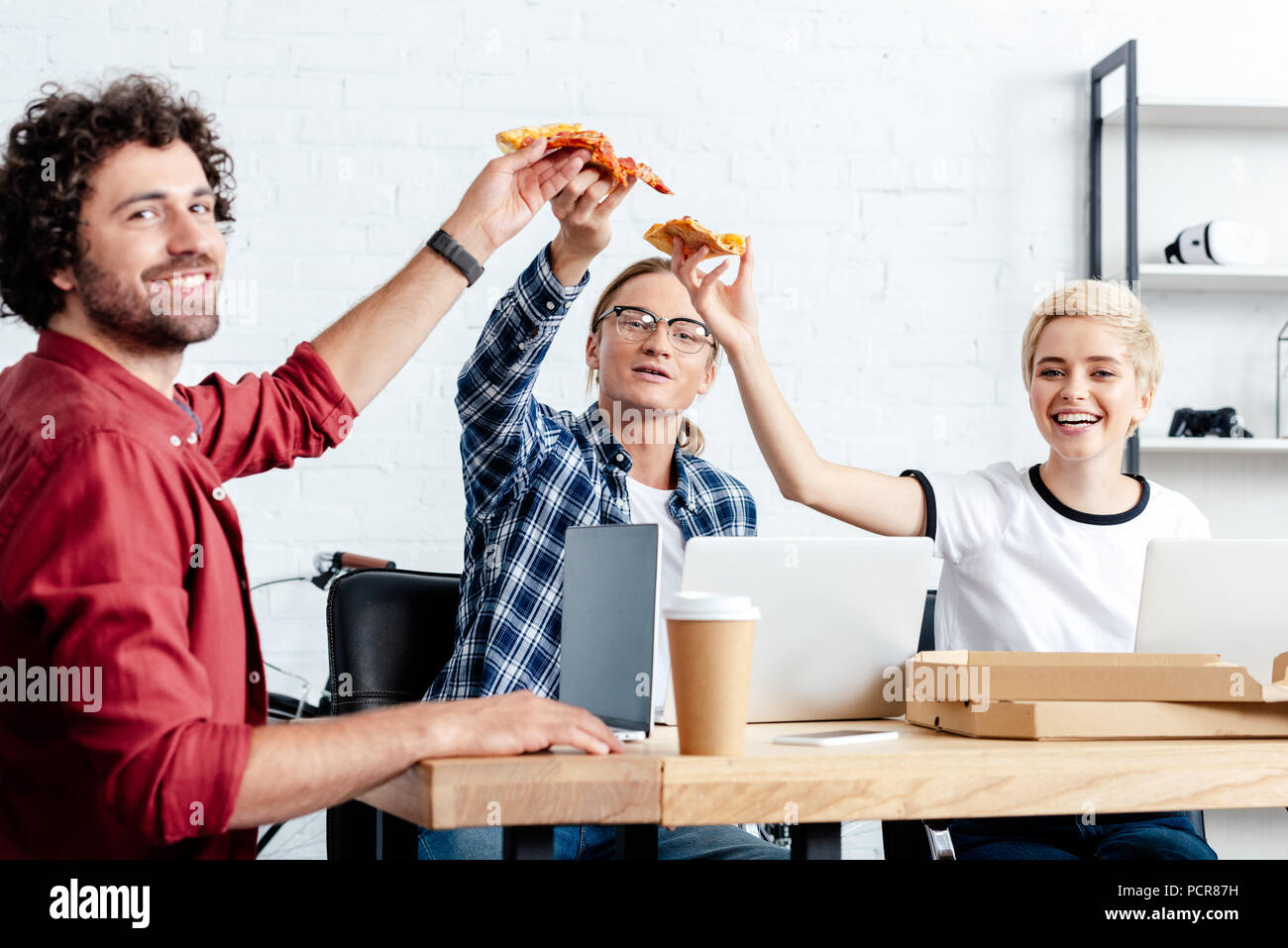 happy young business colleagues eating pizza and smiling at camera Stock Photo