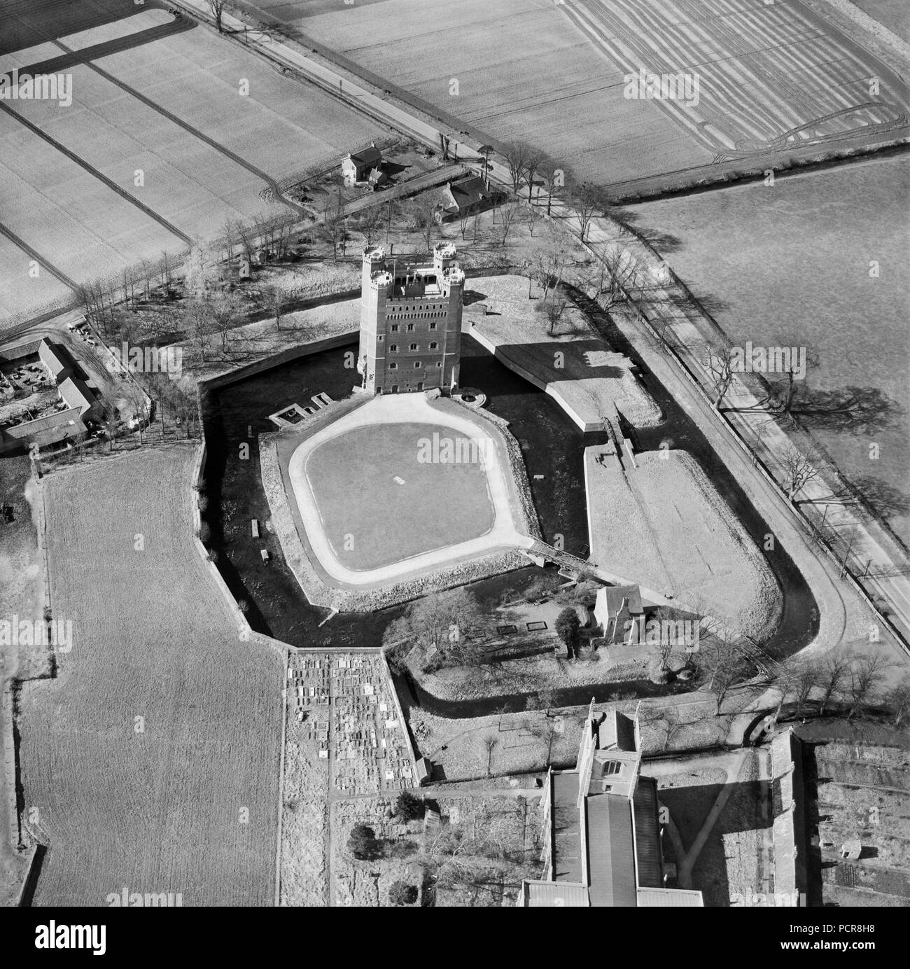 Tattershall Castle, Lincolnshire, 1951. Aerial view of the tower and moats. A rare example of a fortified medieval house, the brick tower was built between the 1430s and 1440s on the site of a 13th century castle. Lord Curzon of Kedleston famously saved it from destruction in 1911 and used it as a catalyst to force key heritage protection legislation through parliament in 1913. - Stock Image