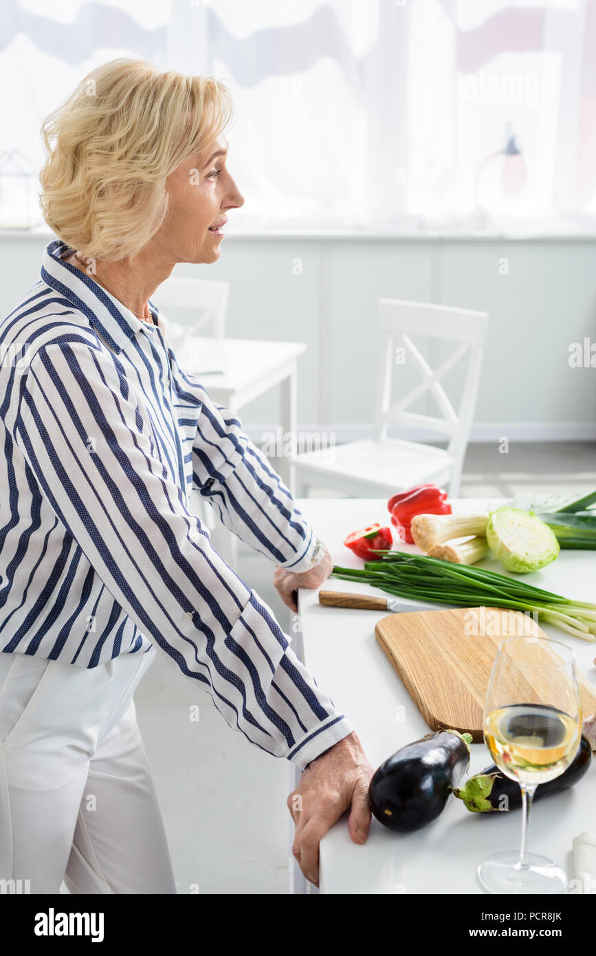 side view of attractive grey hair woman leaning on kitchen counter during cooking in kitchen - Stock Image