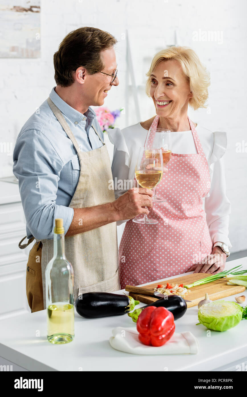 smiling senior couple clinking with glasses of wine during cooking at kitchen and looking at each other - Stock Image
