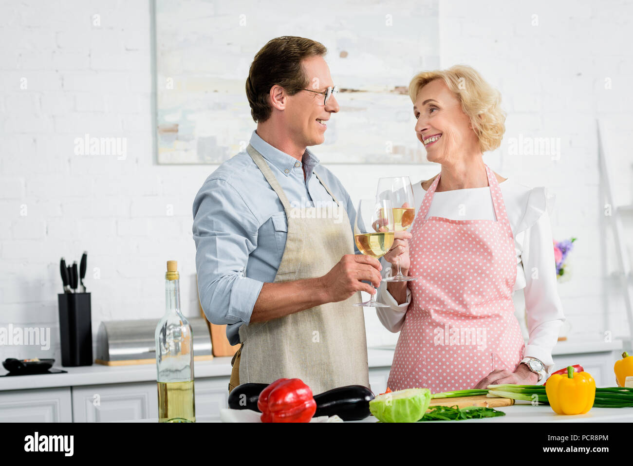 happy senior couple clinking with glasses of wine during cooking at kitchen and looking at each other - Stock Image