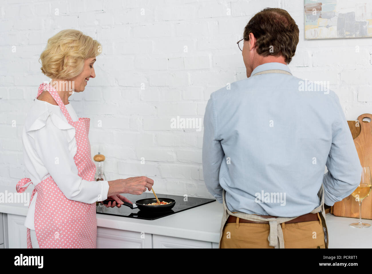 back view of senior couple cooking together at kitchen - Stock Image
