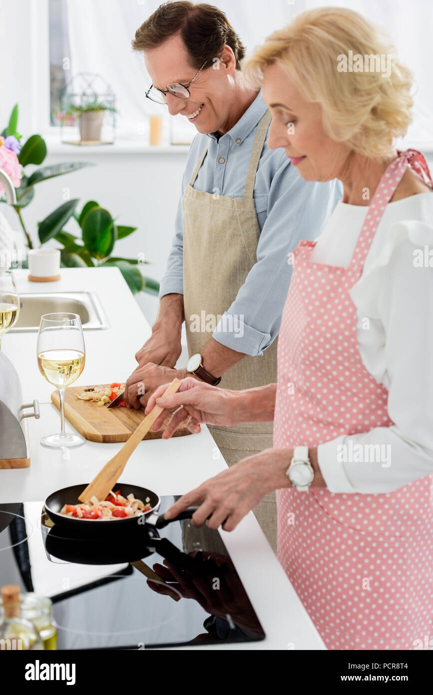 side view of senior couple cooking vegetables on frying pan and cutting vegetables on wooden board at kitchen - Stock Image