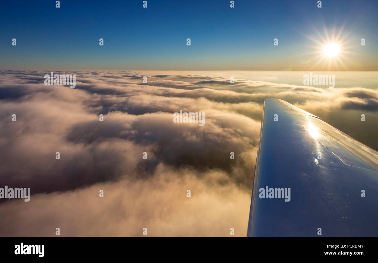 Cloud cover above Winterberg with right airplane wing, sunset, blue sky, Hochsauerland (district), North Rhine-Westphalia, Germany - Stock Image
