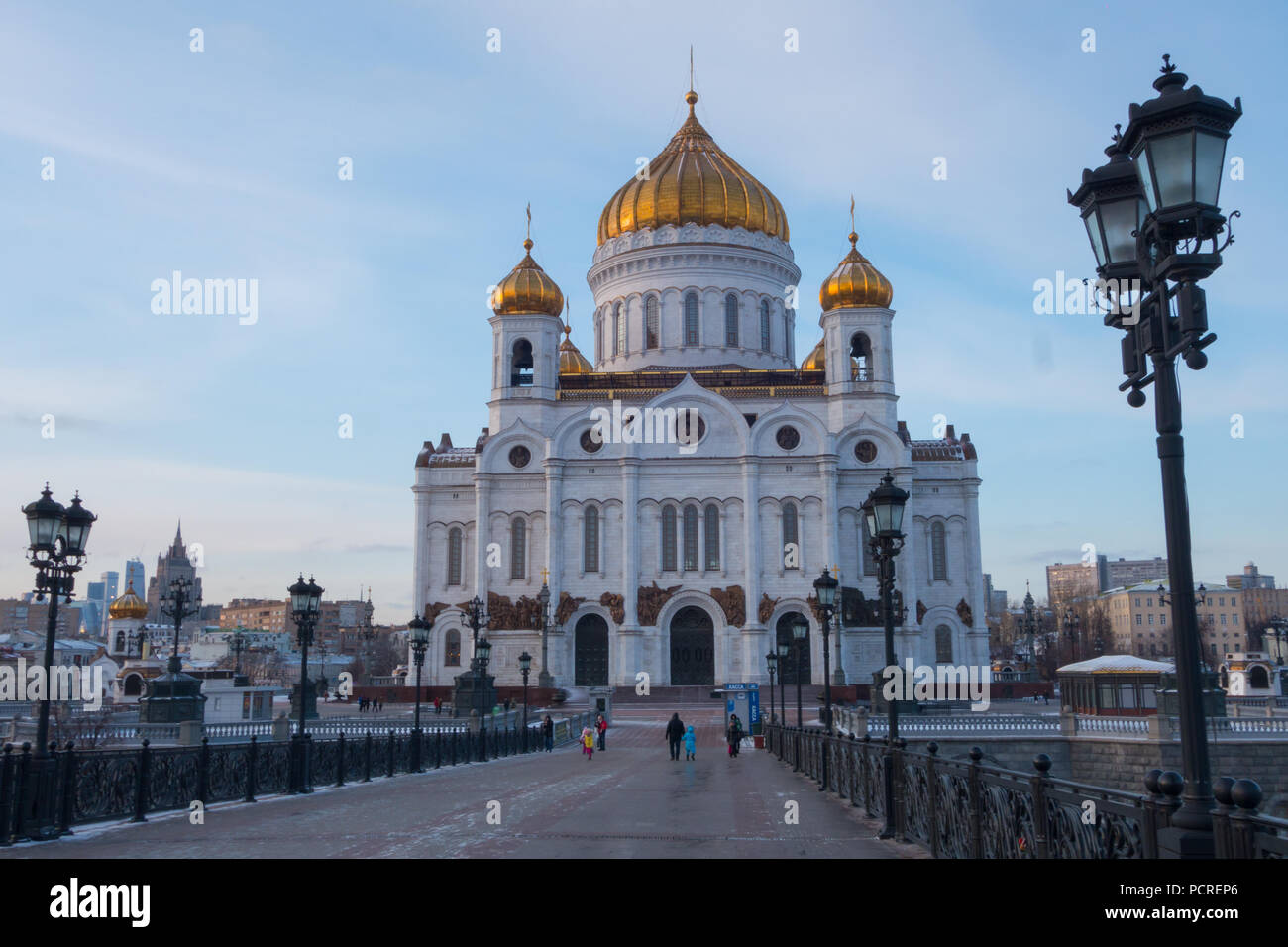 Orthodox church in Moscow, Russia with golden domes and white walls. Street lights in the foreground. Tourists walking towards building. Stock Photo