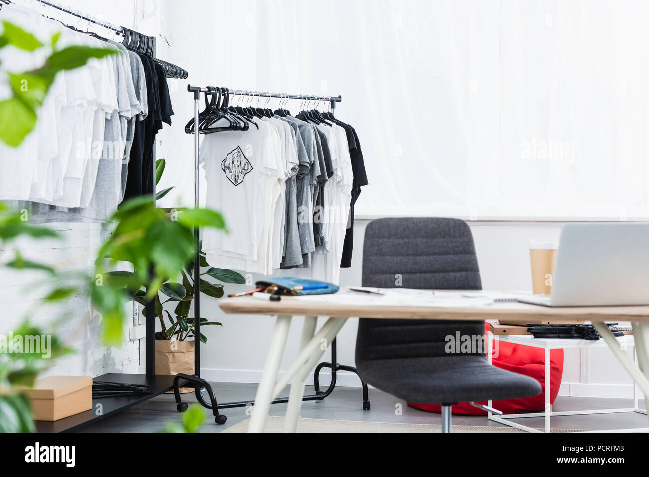 Selective Focus Of T Shirts On Hangers And Working Table With Laptop