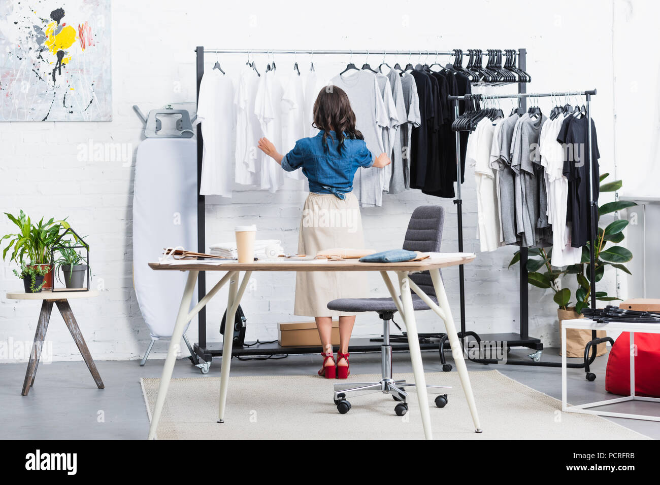 Rear View Of Female Designer Taking Black T Shirt From Hanger In