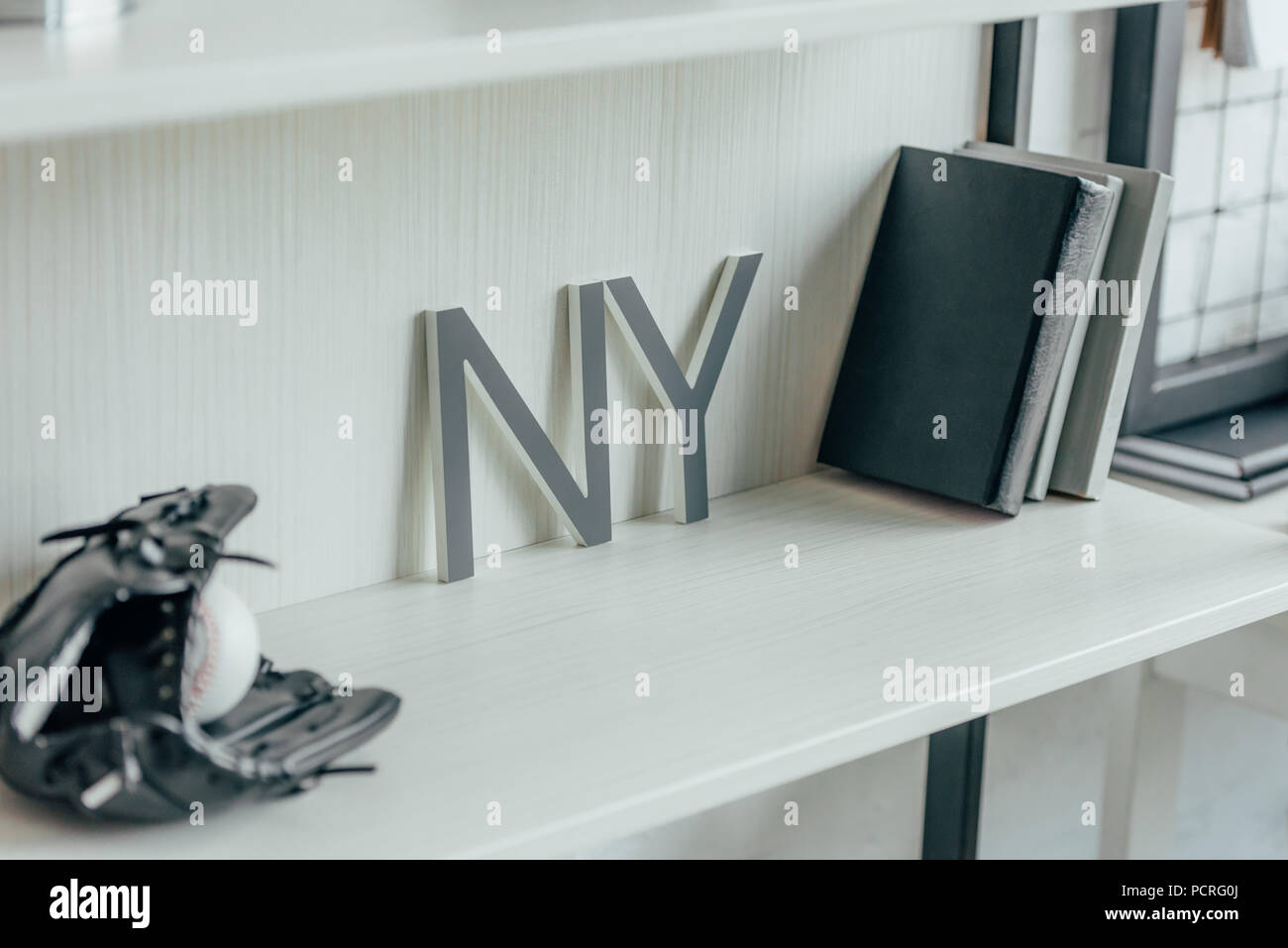 baseball ball, glove and word ny on shelf in office - Stock Image
