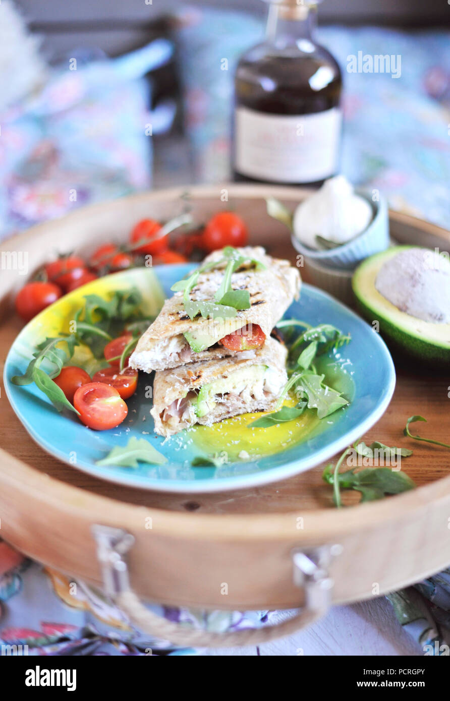 roll of pita bread on the grill. stuffing with fish and salad. avocado and olive oil. dinner on a wooden tray. healthy food Stock Photo