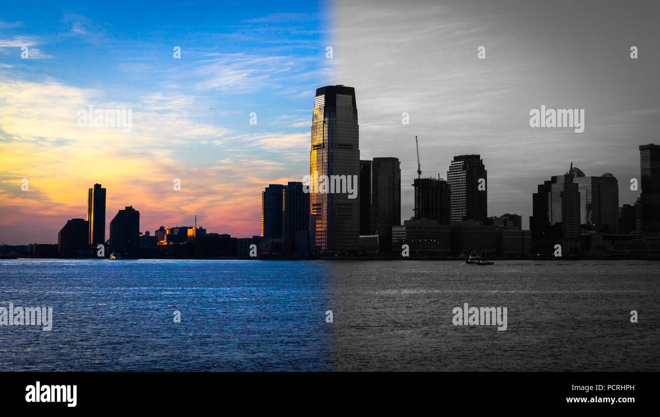 A glowing sunset of shifting colors fills the sky opposite Battery Park, cold winter's evening, turning into vintage B&W version of itself, NYC, USA. - Stock Image