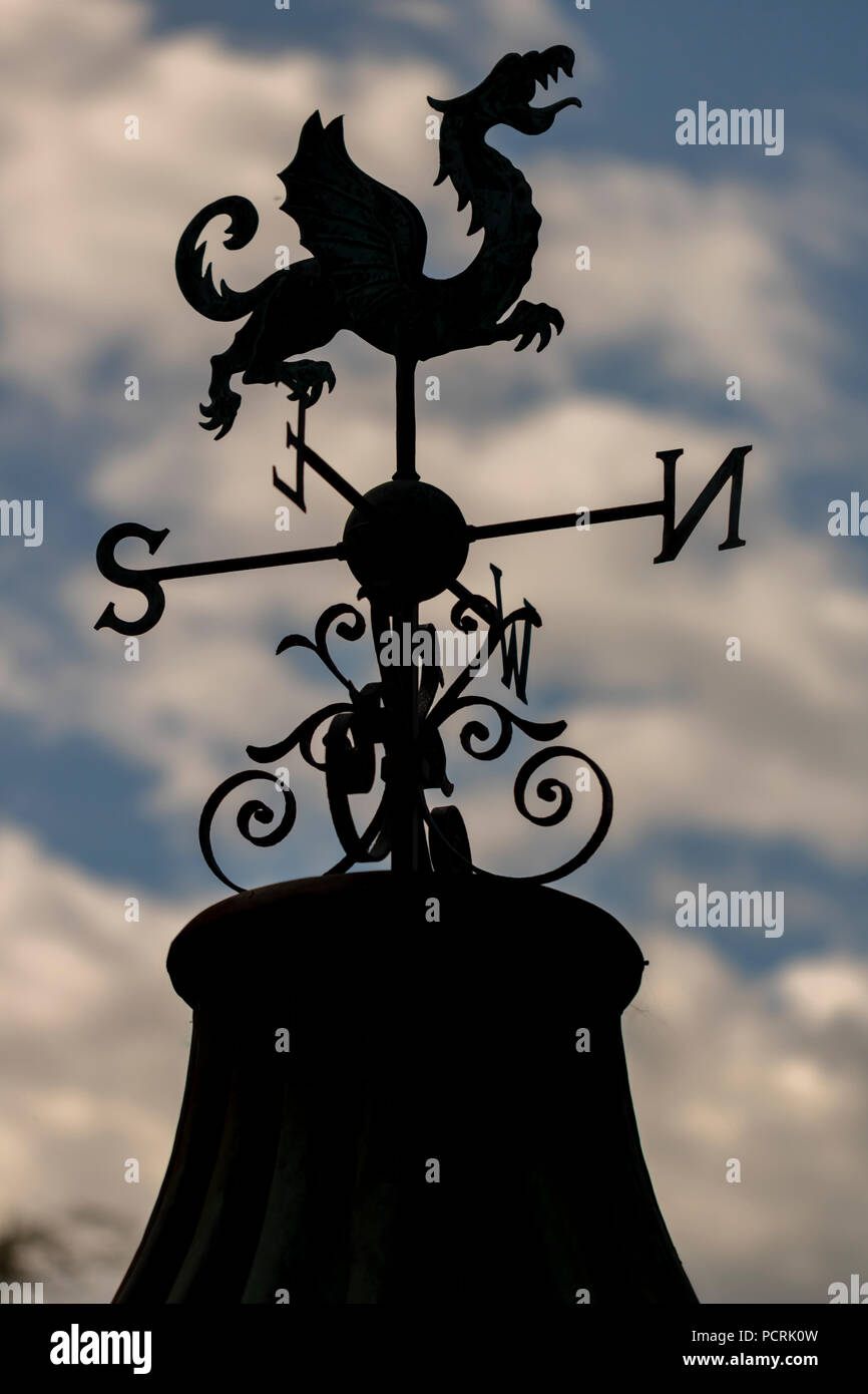 A silhouette of a weather vane with a dragon on top with clouds and blue sky in the background. - Stock Image