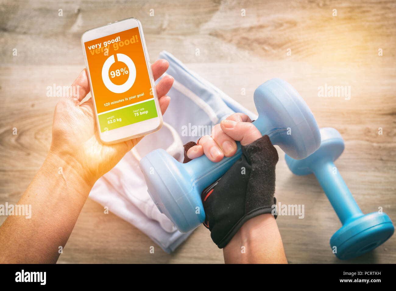 Mobile phone with sport mobile application on screen dumbbels and other sport equipment on a desk - Stock Image