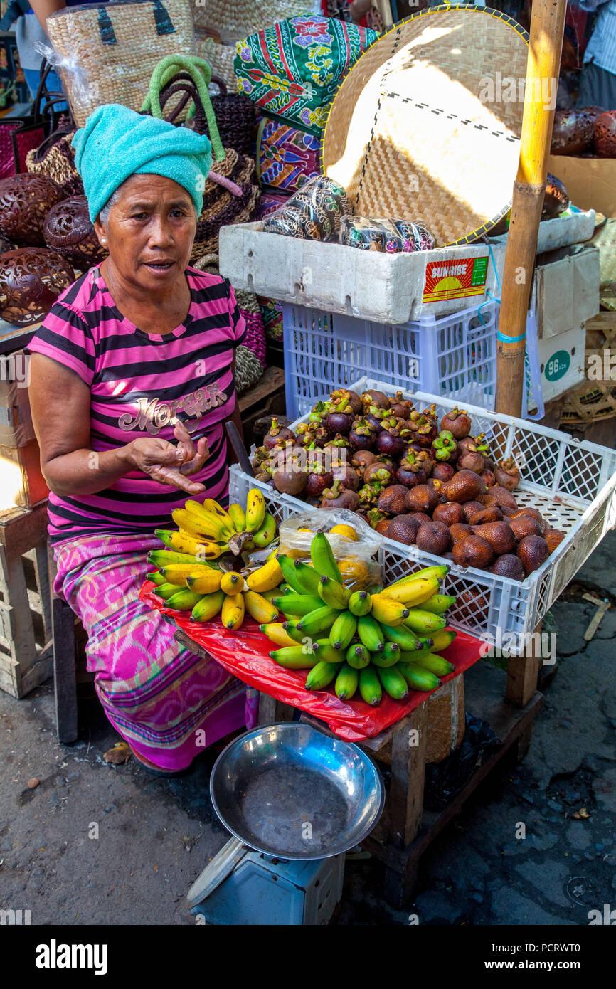 Marketer with bananas (Musa) and salak, snake fruit or snakeskin fruit, Salak palm (Salacca zalacca) fruit, street scene, Ubud, Bali, Indonesia, Asia - Stock Image