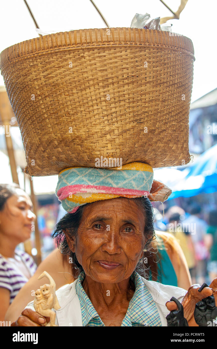 old market woman with a braided basket on her head, Balinese, locals, old woman, Ubud, Bali, Indonesia, Asia - Stock Image