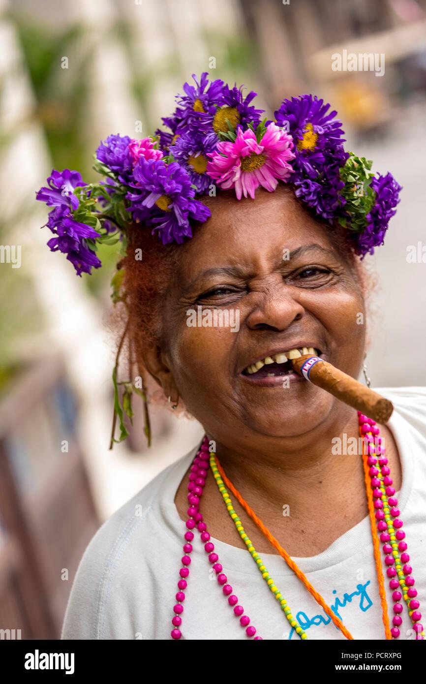old Cuban woman with floral decoration and cigar posing for tourists to receive a tip, La Habana, Havana, La Habana, Cuba, Cuba - Stock Image